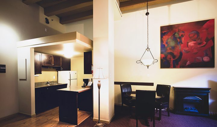 Full kitchen and sitting rooms with chairs and artwork