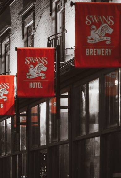 Swans Pub exterior with four logo flags