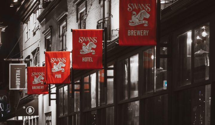 Swans Pub exterior with four logo flags