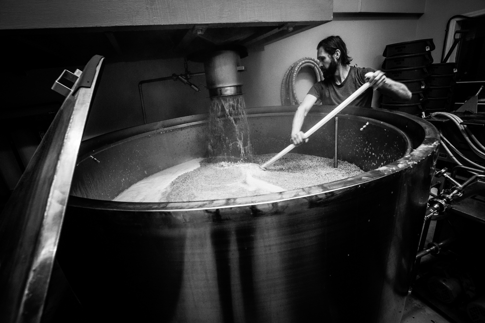 Swans Brewery staff stirring vat of beer